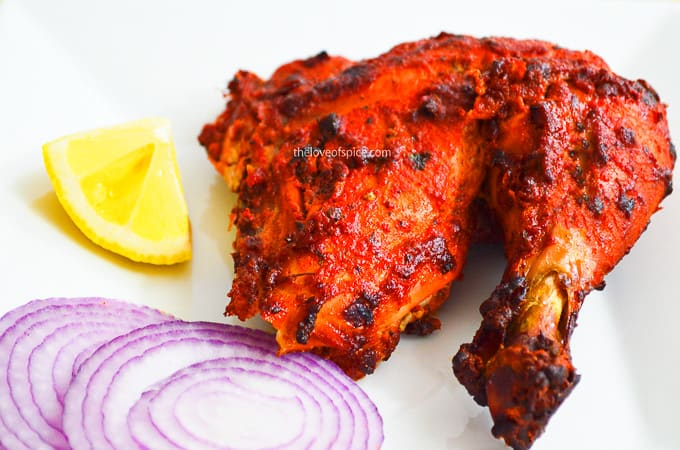 tandoori chicken leg with sliced onions and lemon