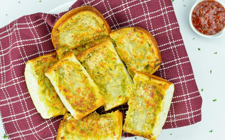 pieces of garlic bread cut from a loaf, set in a bowl, with schezwan chutney dip on the side
