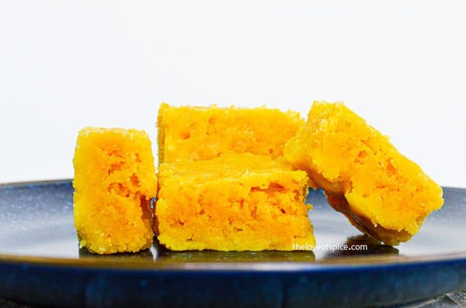 4 pieces of crumbly mysore pak on a blue plate