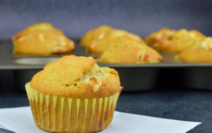 a banana white chocolate chip muffin placed in the front of a tray full of more muffins in the background