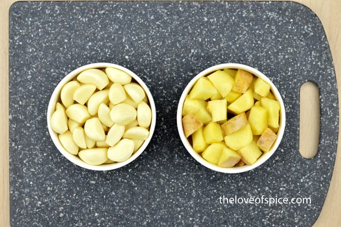 a bowl of ginger cubes and another bowl of garlic cloves