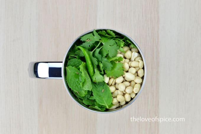 coriander and mint leaves, peanuts, green chilies, and cumin seeds in a mixer jar