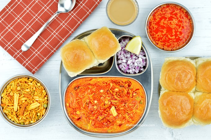 a plate of kolhapuri misal pav served with chopped onions, farsan, tari and tea