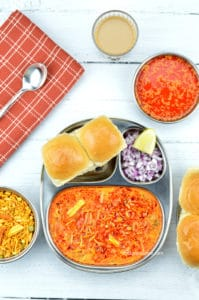misal pav, served in a traditional / sectioned steel plate, along with chopped onions, farsan and kolhapuri tari