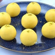 8 besan ladoos garnished with crushed pistachios served in a blue plate
