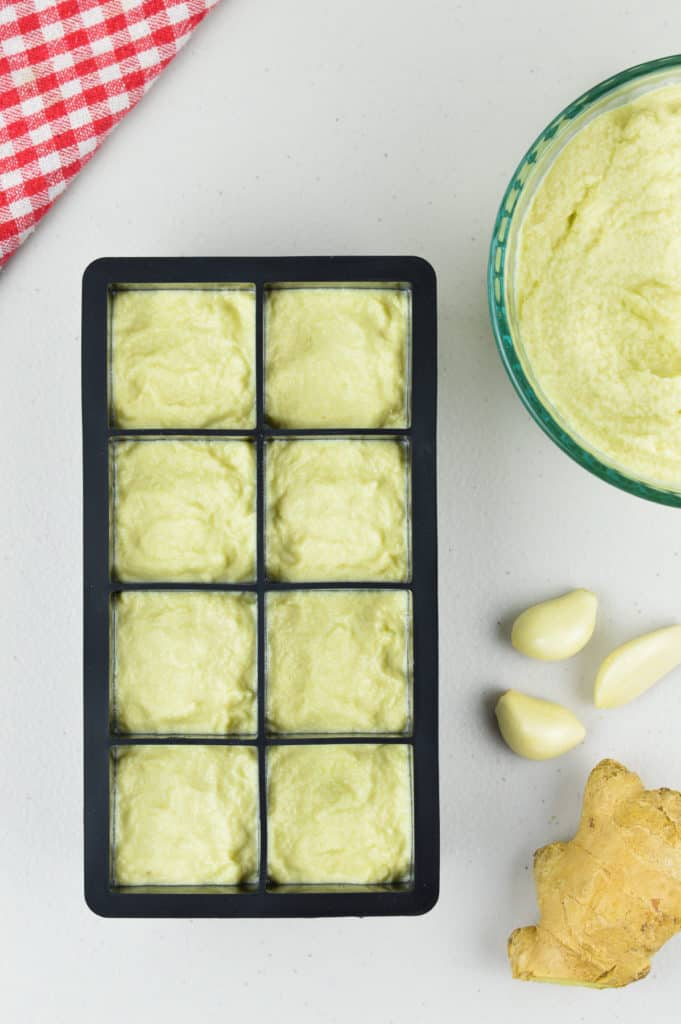 an ice cube tray full of ginger garlic paste to be frozen, with a fresh bowl of ginger garlic paste, and some fresh ginger and garlic on the side
