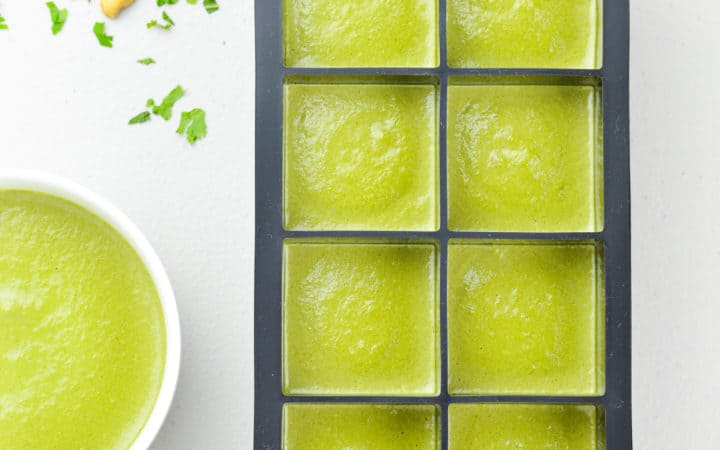 an ice cube tray full of coriander mint green chutney to be frozen, alongside a fresh bowl of green chutney