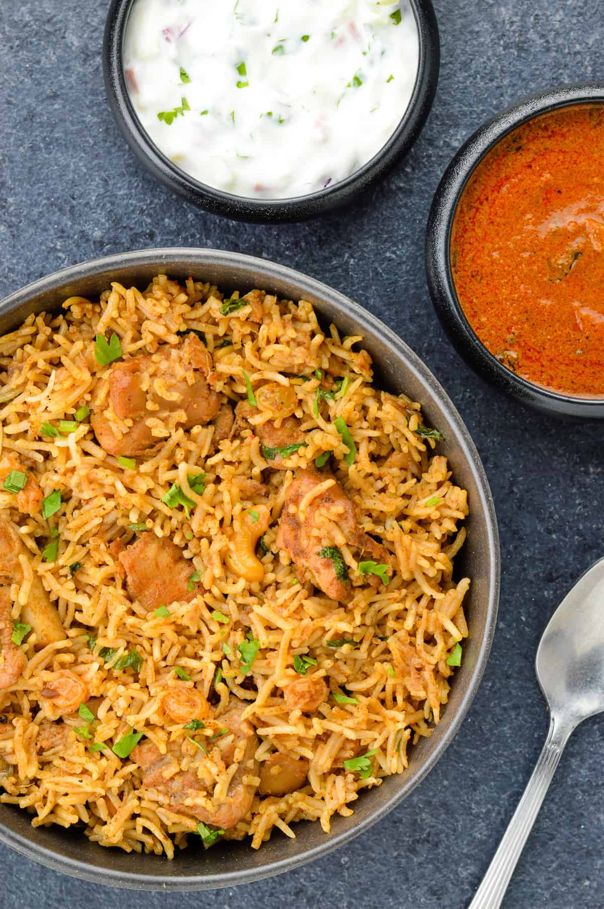 chicken biryani served on a plate, along with a bowl of yogurt, bowl of indian curry, a glass of water, and lemon wedges on the side