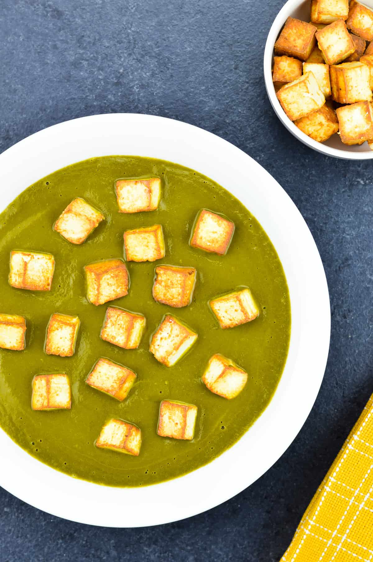 homemade palak paneer served in a big wide white bowl with extra pan fried paneer cubes in a bowl on the side