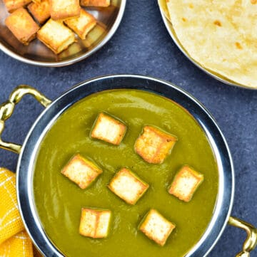 palak paneer in traditional indian serving kadai, with homemade chapatis, and extra pan fried paneer cubes on the side