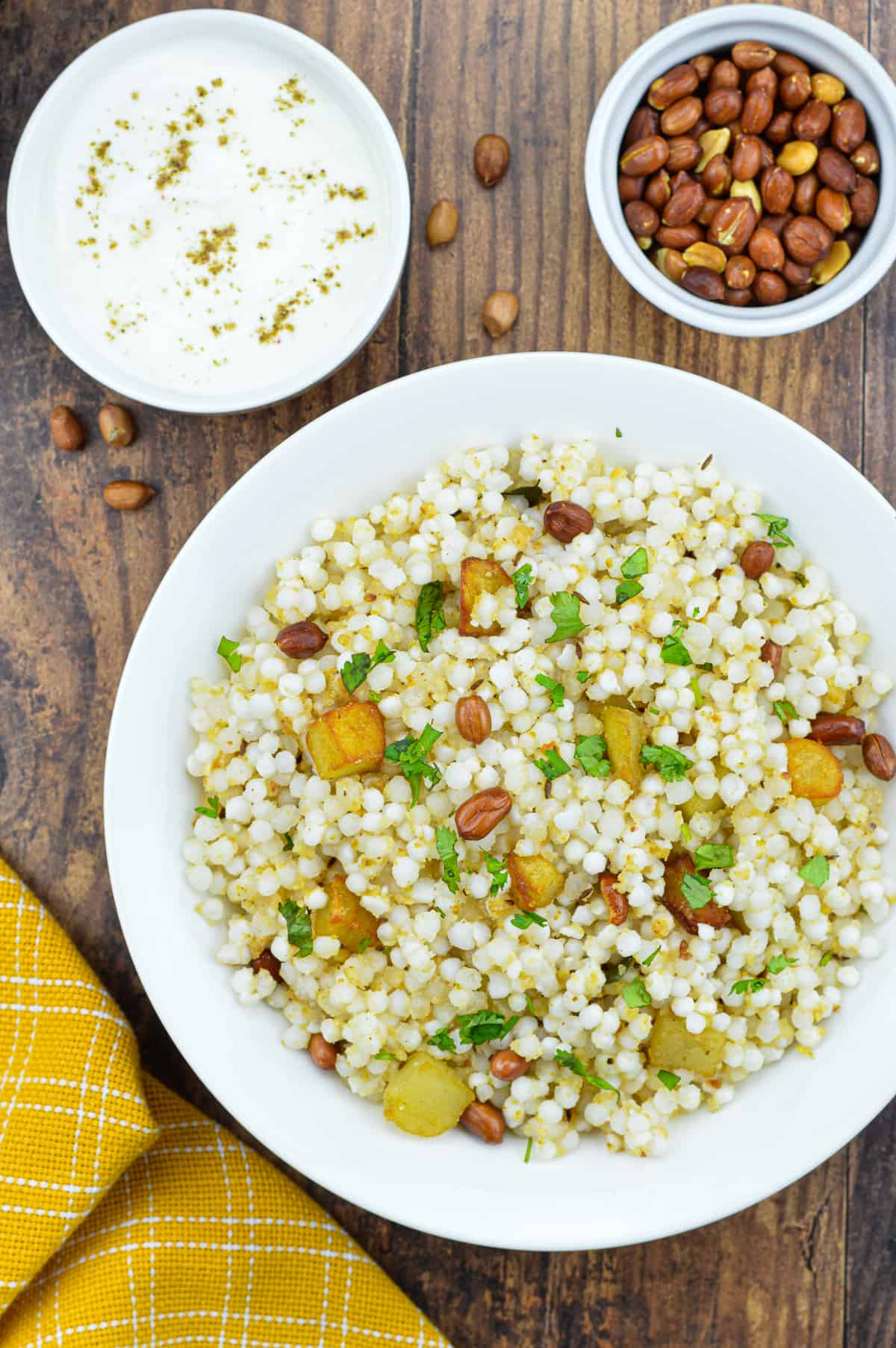 a plate full of sabudana khichdi, with a bowl of roasted peanuts, and a bowl of yogurt on the side