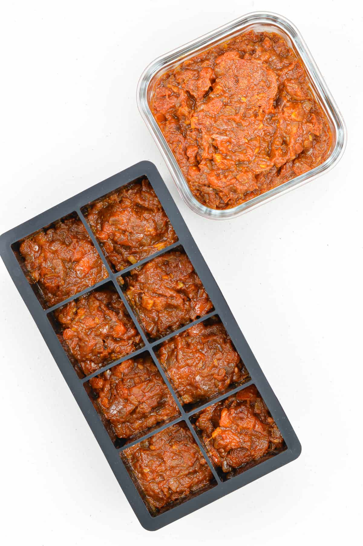 bhuna masala curry sauce base portioned out in a black ice cube tray and also in a glass storage container
