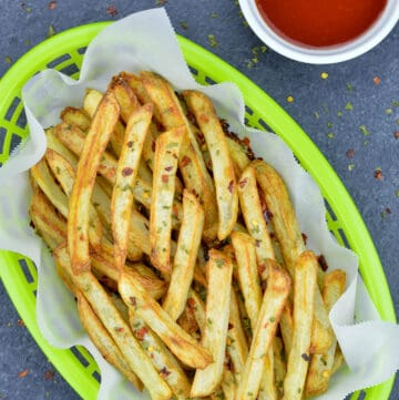 air fried french fries in a green fast food serving basket, with a small bowl of ketchup on the side
