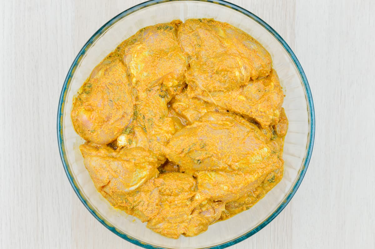 photo of chicken leg quarters marinated in a glass bowl with indian spices and flavorings