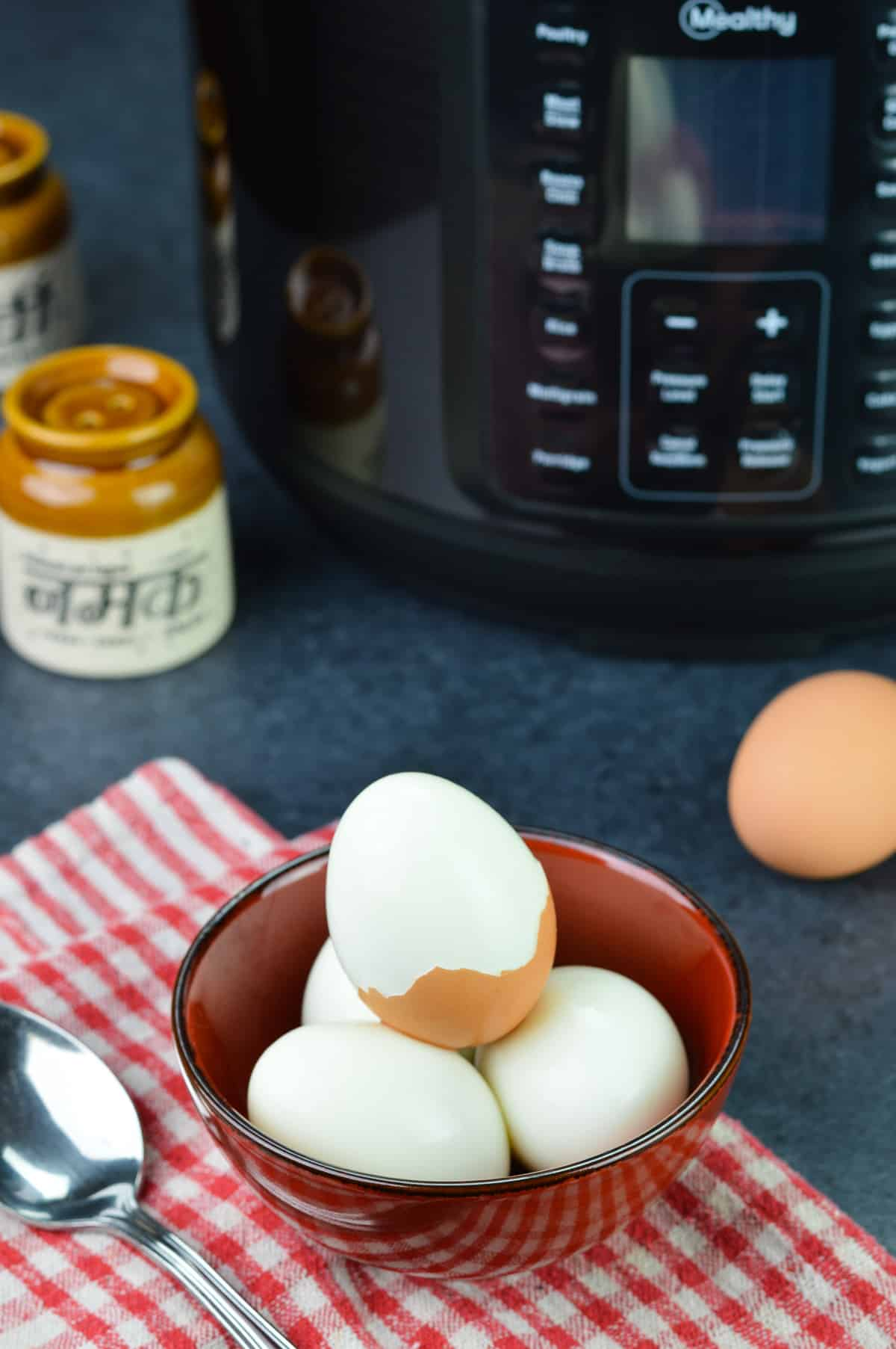 a bowl of hard boiled eggs, with one egg half peeled, along with mealthy multipot 2.0, an unpeeled egg, and salt & pepper shakers in the background