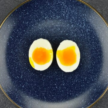 a blue plate with one soft boiled egg, which is cut open vertically into two