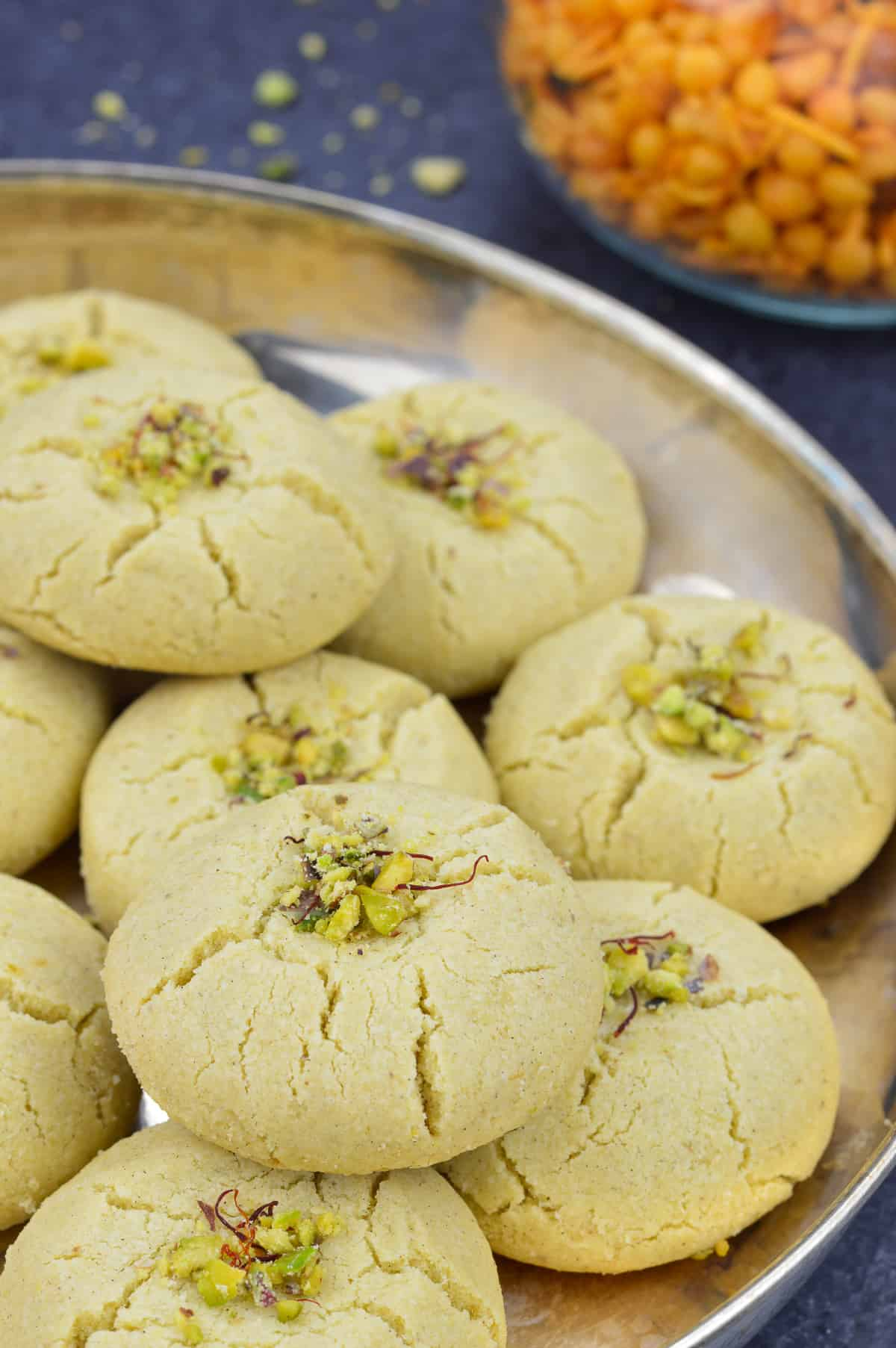 a plate of nankhatai biscuits garnished with pistachios and saffron strands, with indian snacks in the background