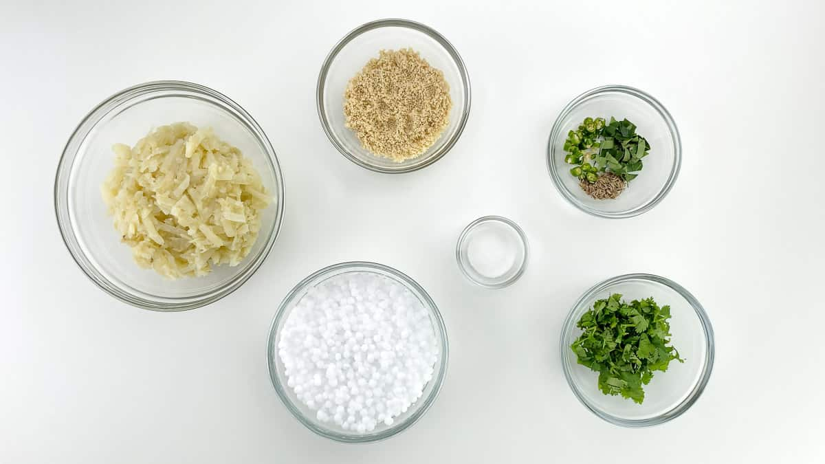top shot of all the ingredients to make sabudana vada, along with ingredient labels