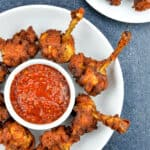 chicken lollipops placed around a small bowl of schezwan chutney in a white plate, with a few more lollipops visible in the background