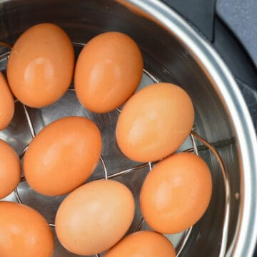 top close up shot of large brown eggs placed on a trivet in the instant pot