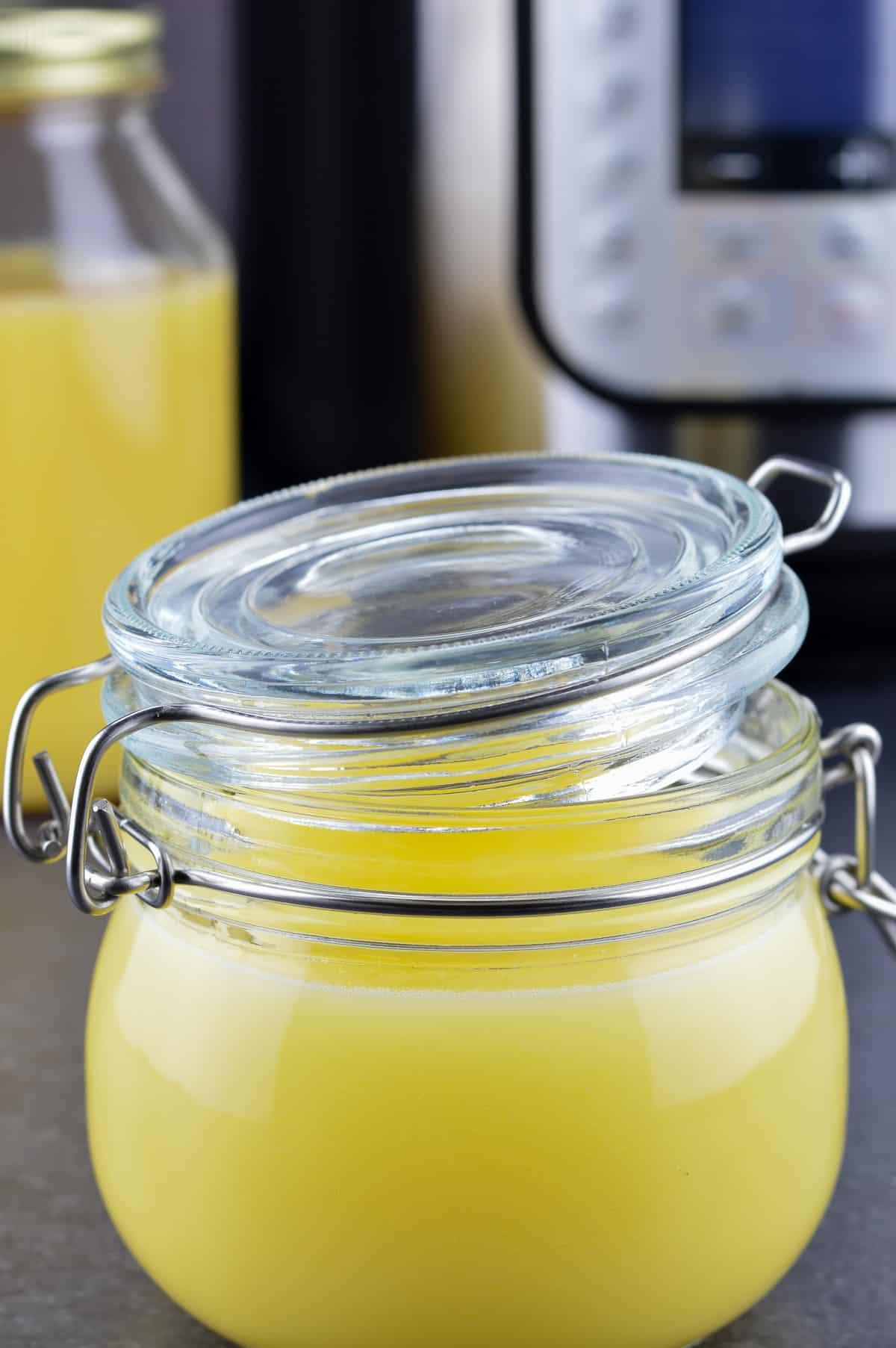 Instant Pot ghee in a small glass jar, and another bottle of ghee & Instant Pot in the background