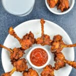 chicken lollipops placed around a small bowl of schezwan chutney in a white plate, served along with a drink, and a few extra lollipops on the side