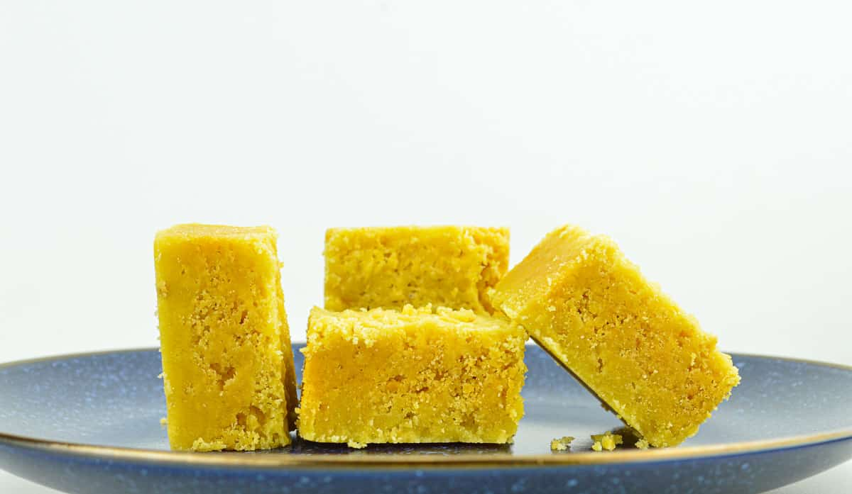 close up of 4 pieces of mysore pak placed on a blue plate