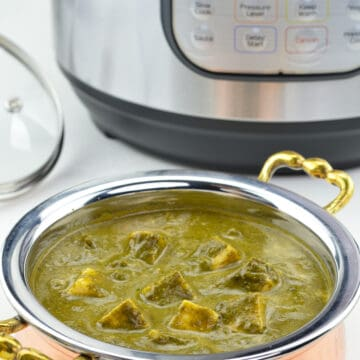 a close up shot of kadai full of palak paneer made in instant pot, with an Instant Pot in the background