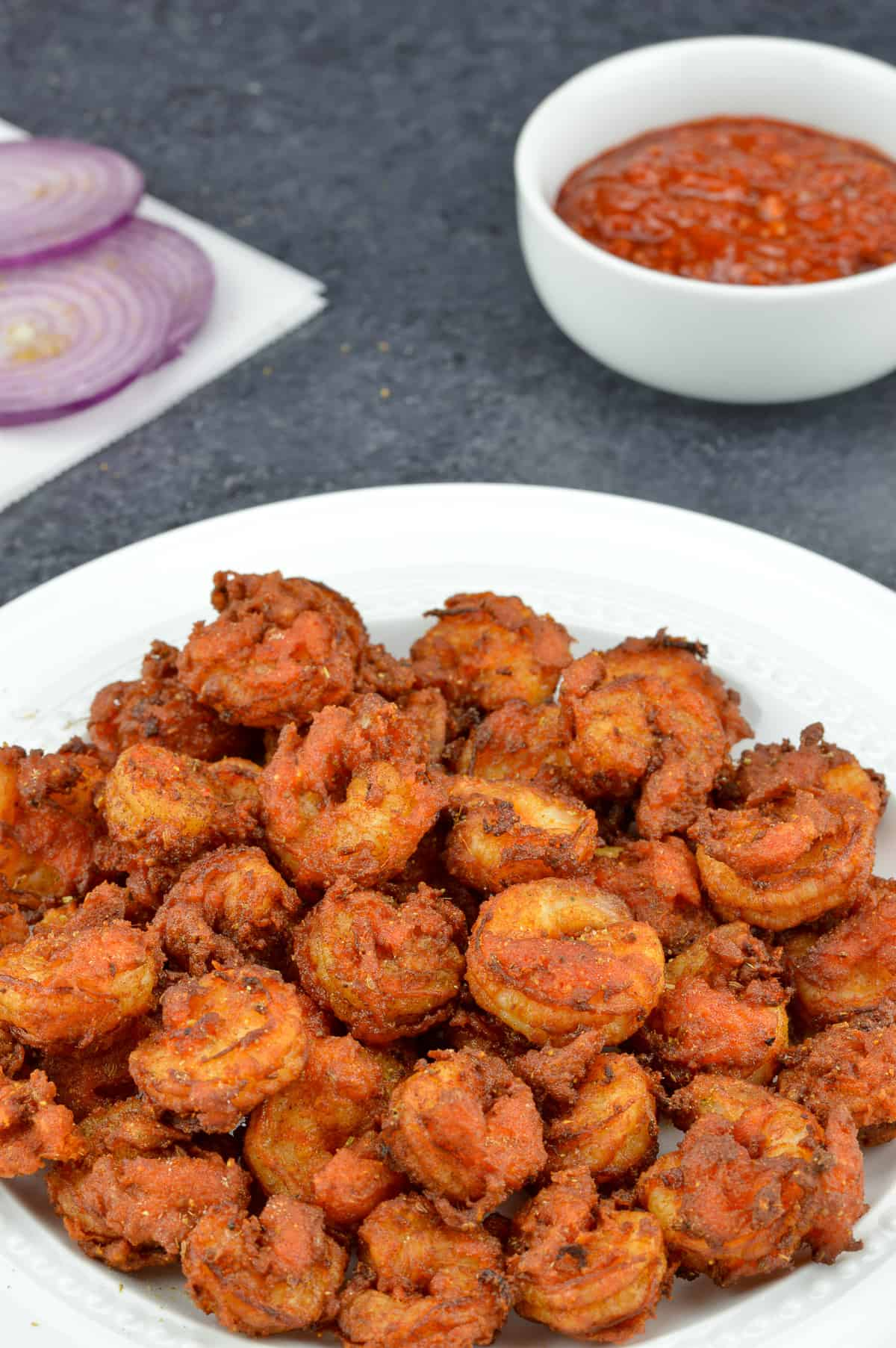 crispy fried prawns koliwada sprinkled with chaat masala, served in a white plate, along with schezwan chutney, and sliced onions in the background