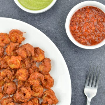 mumbai style prawns koliwada sprinkled with chaat masala, served in a white plate, along with a fork, green chutney, and schezwan chutney on the side