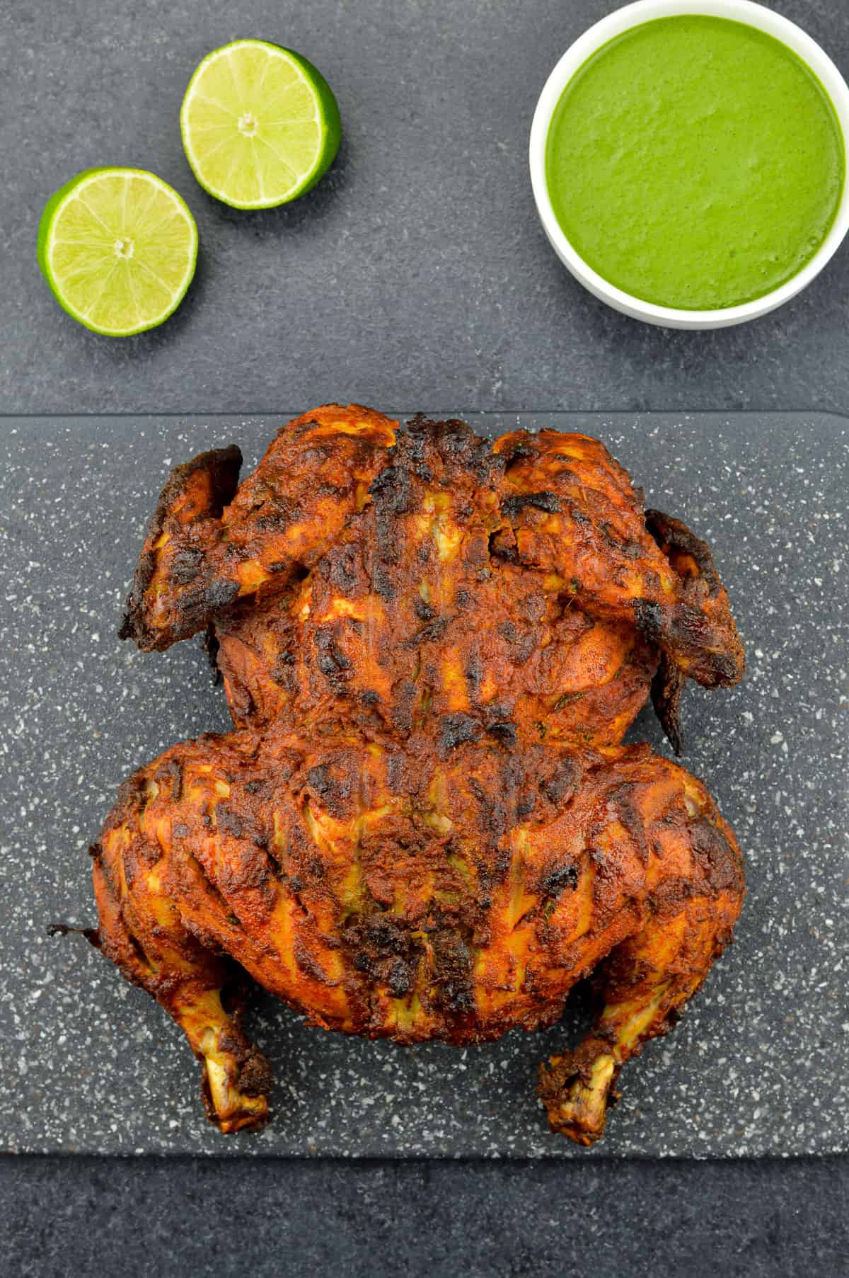 a whole chicken tandoori placed on a black cutting board, with a bowl of green chutney and a couple of lemon wedges on the side