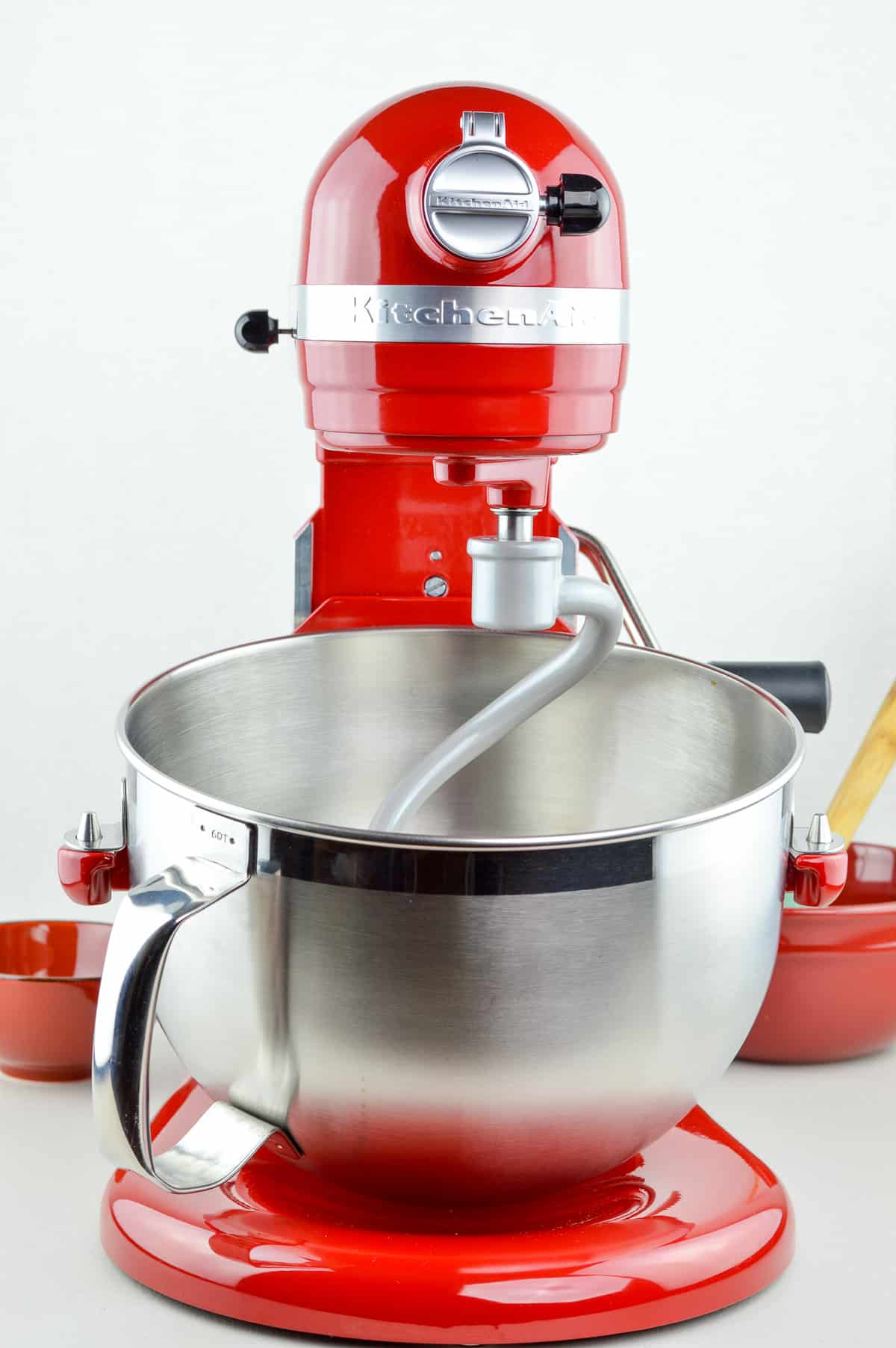 a close up shot of red colored 6 quart KitchenAid Professional stand mixer