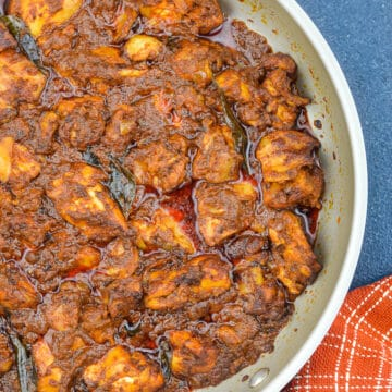 top shot of chicken ghee roast in a pan, with a kitchen towel on the side