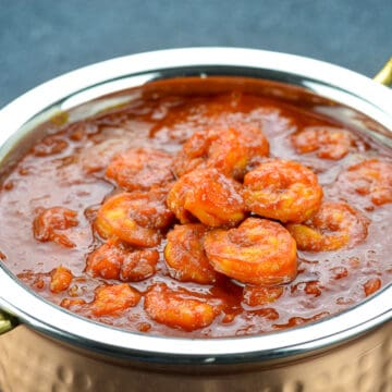 a close up shot of a serving kadai full of mangalorean prawns curry