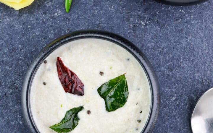 top shot of two bowls of white coconut chutney (with a spoon, and 2 green chillies & pieces of ginger on the side)