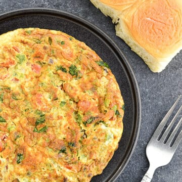 indian style masala omelette served in a plate, with 2 Indian style ladi pav on the side