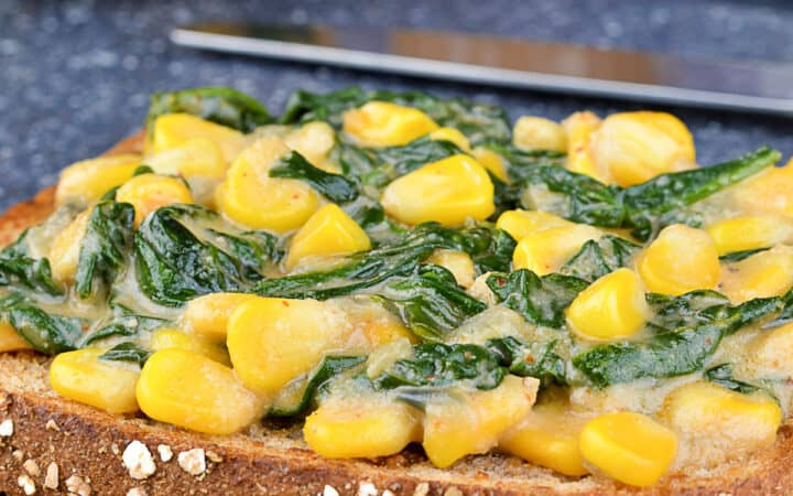 open faced spinach corn sandwich on cuttting board, with additional sandwich filling and tea in the background