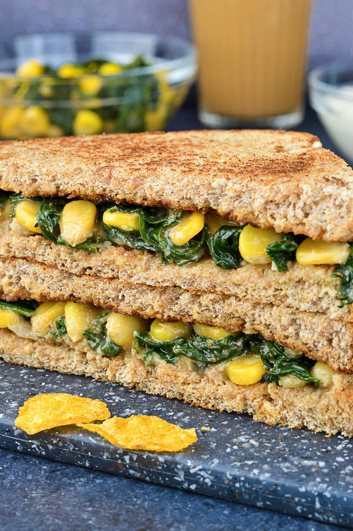 close up of stacked halves of spinach corn sandwich, with additional sandwich filling and tea in the background