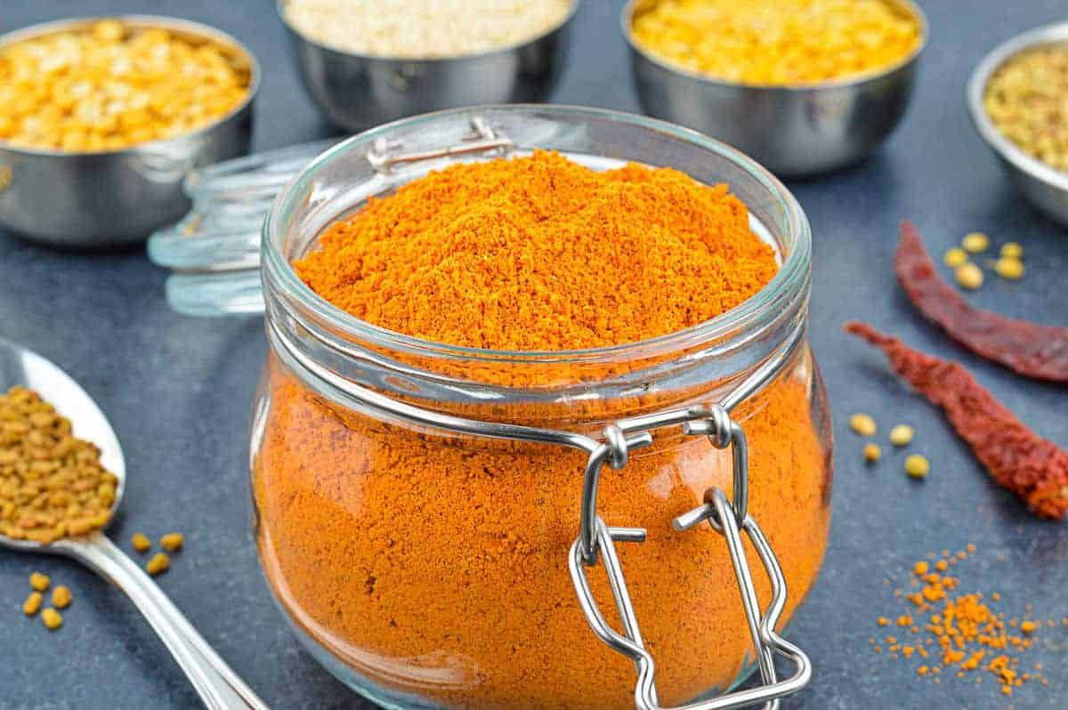 an open glass jar of sambar masala powder, with the ingredients used spread out in the background