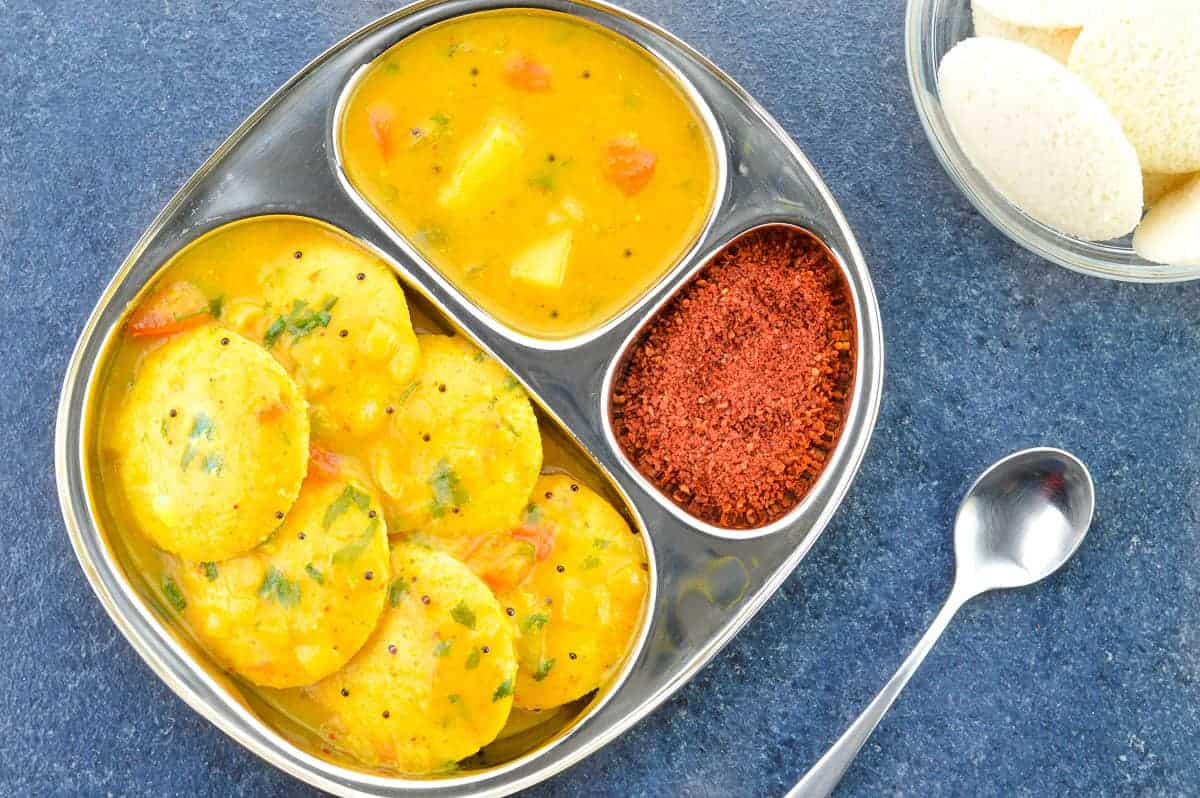 top shot of a plate full of idlis dunked in sambar, with more sambar on the side, along with podi or dry chutney for idli
