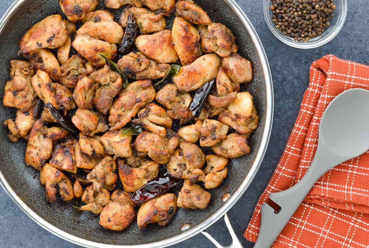 top shot of a pan full of pepper chicken dry, with a serving spoon, and black peppercorns on the side