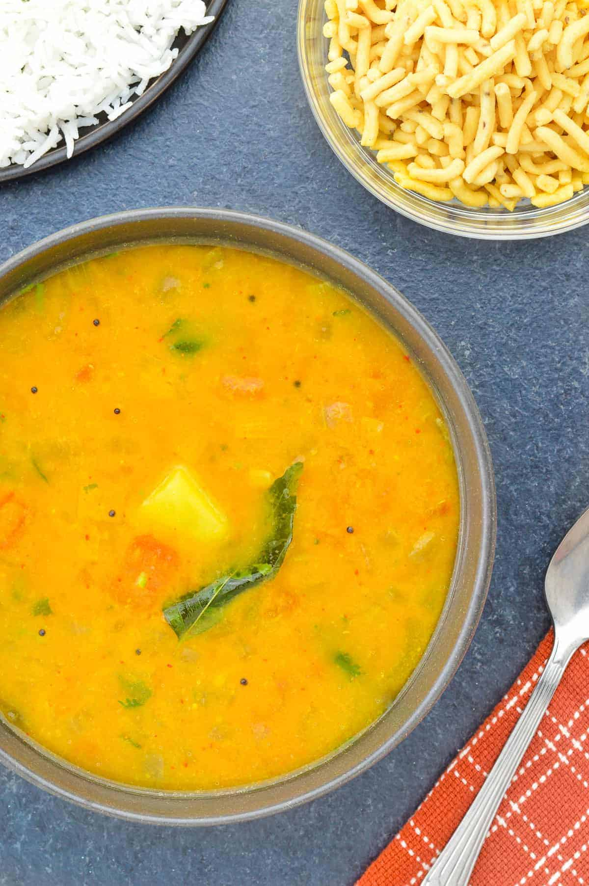 top shot of a bowl of homestyle sambar, with a plate of rice, small bowl of bhavnagari, and a spoon on the side