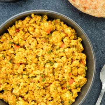 top shot of a bowl full of paneer bhurji, with a roti on the side, along with a spoon & some sliced onions